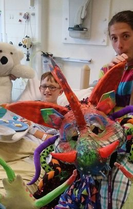 2Faced Dance's colourful dragon and two other performers interact with boy in bed