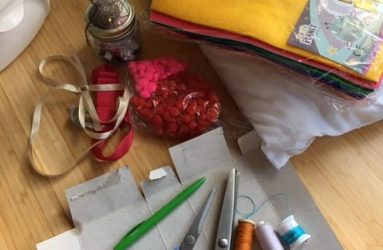 materials and equipment laid out including scissors, thread, felt and ribbon