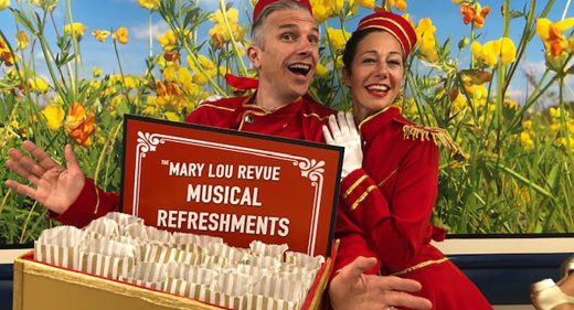 Performers dressed in red as ushers with tray of 'musical refreshments'