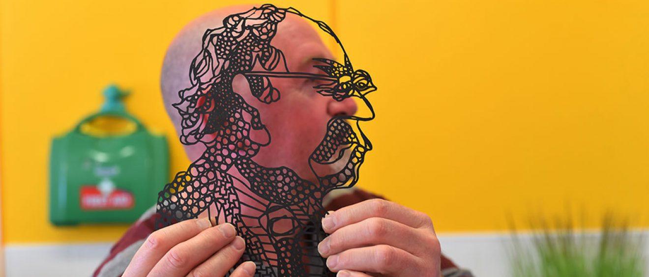 Man holds up outline black and transparent image of himself alongside his own side profile