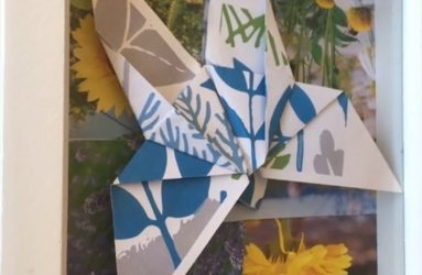 folded paper butterfly framed in box frame with collage of flowers behind