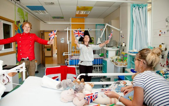 Actors dressed as pirates waving flags, parent and child on ward watching