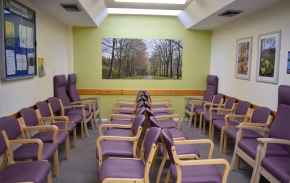 Large scale artwork of avenue of trees at end of waiting area, with lilac seating in front
