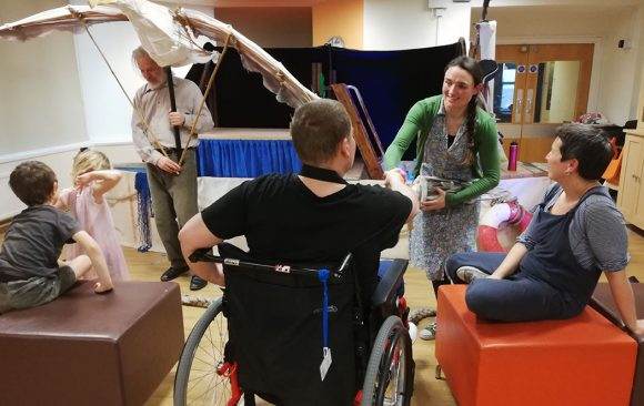 Performer showing Albatross puppet to adult in wheelchair