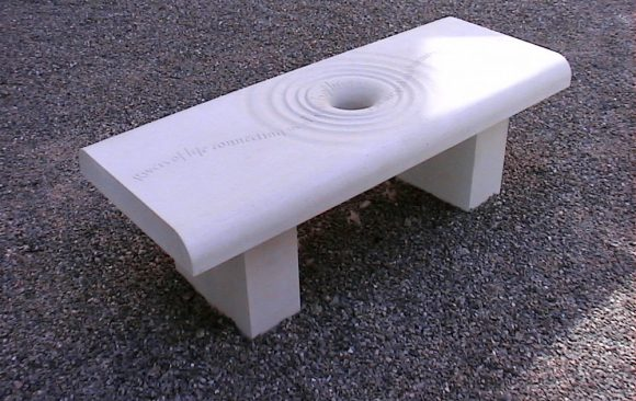 Carved stone bench with hole in centre and concentric circles like ripples, line of poetry