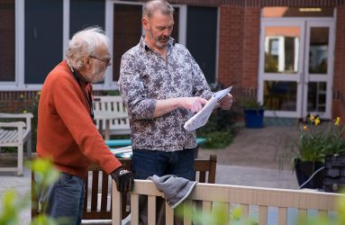 Volunteer looking at plans for garden with ArtCare technician