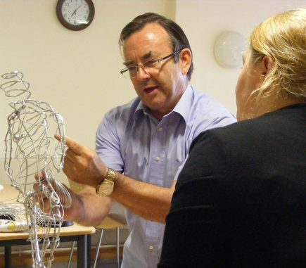 Martin working on wire figure with staff member