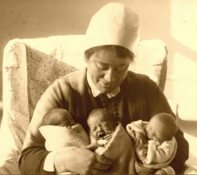 Nurse cradles three new born babies