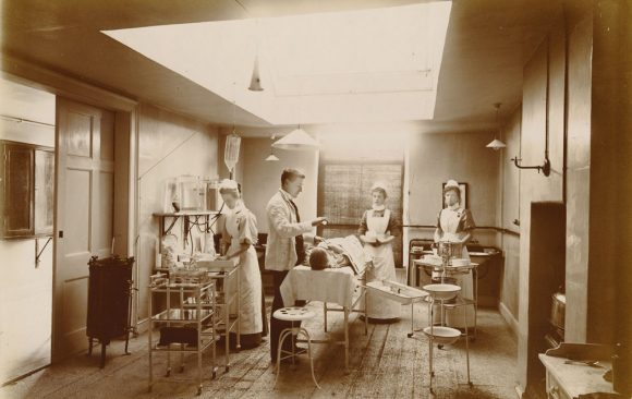 Doctor anaesthetising patient, nurses in attendance