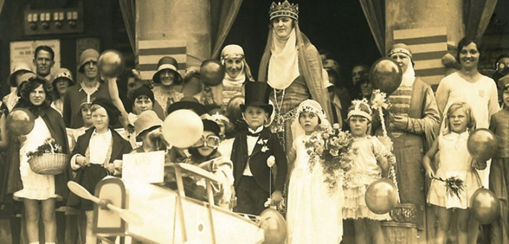 children and adults dressed up in costumes holding balloons