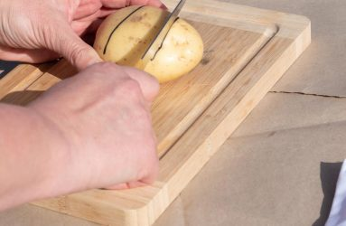 cutting two large chunks of end of potato with knife