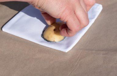 press paint covered edge of potato onto bag