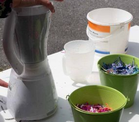 switching on the blender containing shredded paper and water