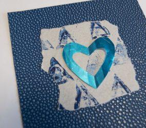 blue cut out heart layered onto blue monoprint