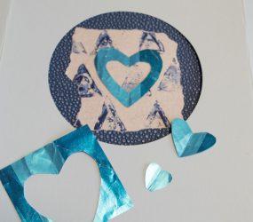 cut out blue foil hears on blue monoprint