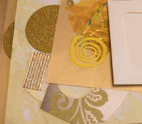 pile of paper, gold card, and yellow shapes