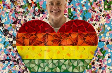 photo of Damien Hirst holding rainbow heart shape with butterfly shapes