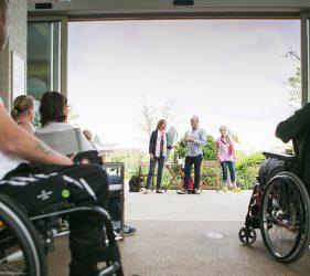 Audience members in wheelchairs watching the performers