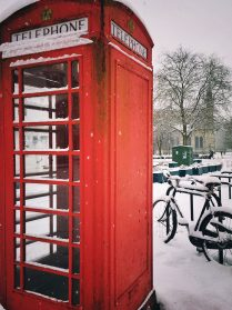 Photo of red telephone box next to a bike with cathedral in the background in the snow