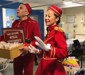 Performers dressed as vintage cinema usherettes performing at the bedside