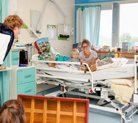Mum and boy in hospital bed watching the actors in the show