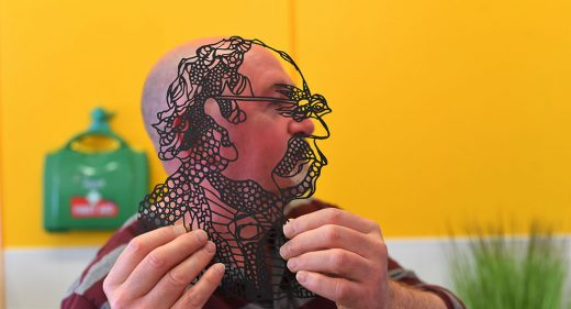 Man holds up outline black and transparent image of himself alongside his own side profile