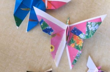 different sized folded paper butterflies in several different coloured papers