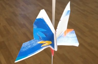 folded paper butterfly suspended on a ribbon
