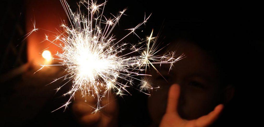 hands holding a sparkler in the dark