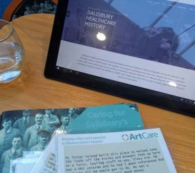History book, postcard memories and website visible on tablet