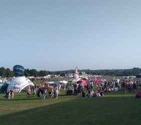 Crowd of people in field, event tent, blue sky