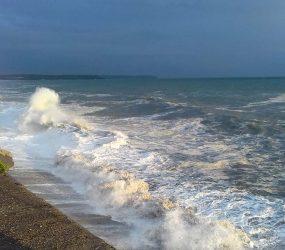photograph of waves crashing against sea wall