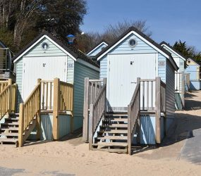 photograph of pastel coloured beach huts with wooden steps leading up to doors