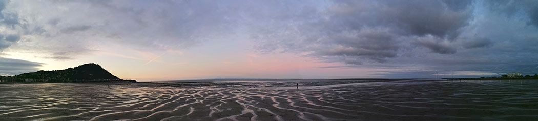 panoramic photo of shoreline, vast mudflats, headland on left with sun setting