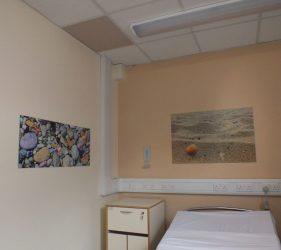 Beach themed artworks and coloured ceiling tiles above bed