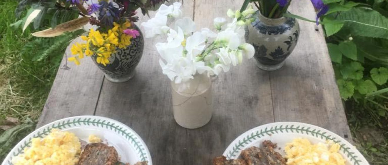 scrambled eggs and bread on plates on outside table set with flowers in vases