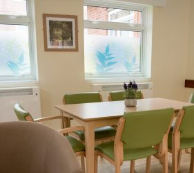 View of the dayroom showing new table, chairs, print of lane on wall and fern silhouette window film