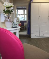 Pink and beige chair, wood effect flooring, white wardrobe and side table with flower