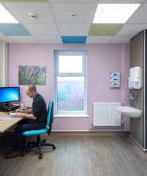 Photographic artwork of lavender on wall of consulting room, wood effect flooring, bespoke design window film and coloured ceiling tiles