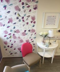 Floor to ceiling artwork panel with rose and leaf design and blue tit. White side table and pink and beige chair in foreground.