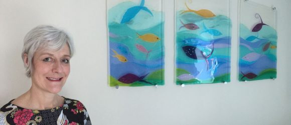 Sue King with her tryptich of fused glass panels showing fish amongst waves
