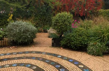 Ceramic stepping stones arranged with beige mosaic tiles to form circle path feature in garden