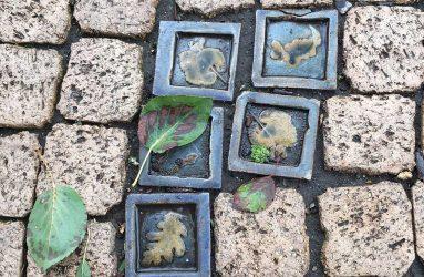 Square leaf ceramic tiles amongst plain mosaic path tiles