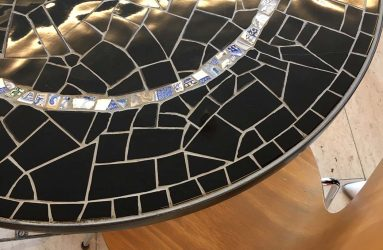 Black mosaic table top with circle of blue and white tile as feature in cafe
