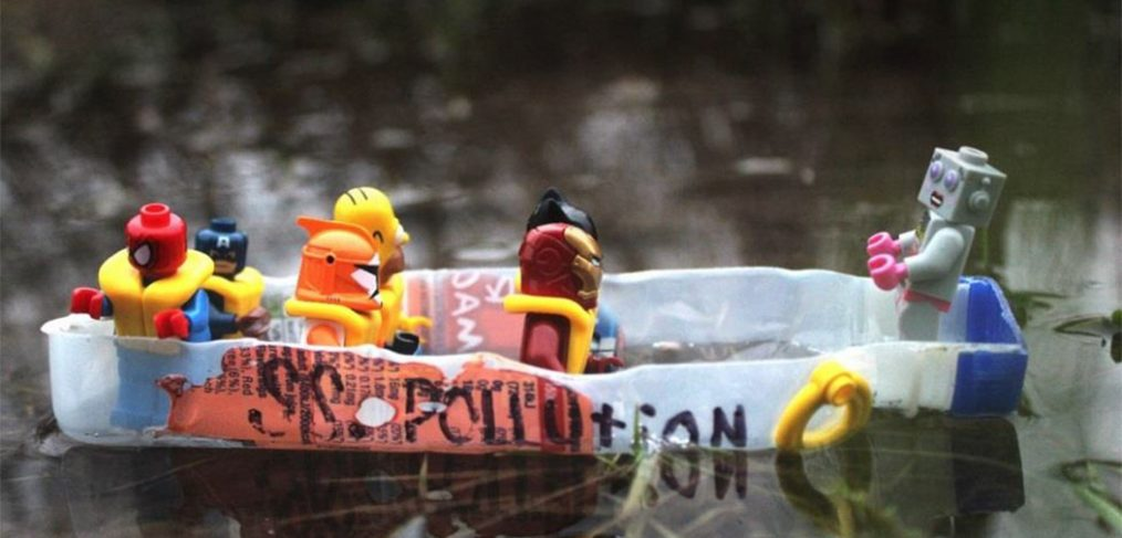 Photo of lego figures with life jackets on plastic raft (cut up plastic bottle) on water