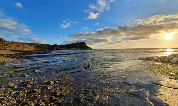 sun rising over Kimmeridge bay, low tide foreground, cliff in distance
