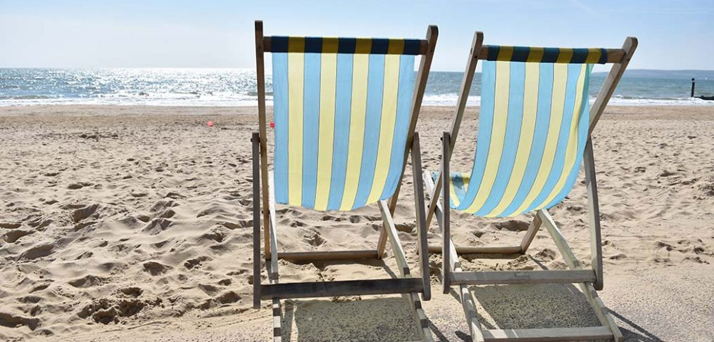photograph of two blue and yellow deckchairs on the beach