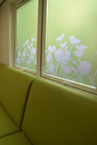 Window film design with flower silhouette on green background