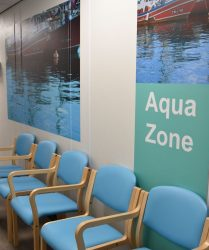Light blue coloured seating with aqua wall panel and lake artwork