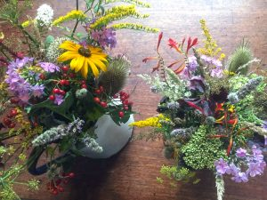 jugs full of colourful wild flowers, thistles and berries